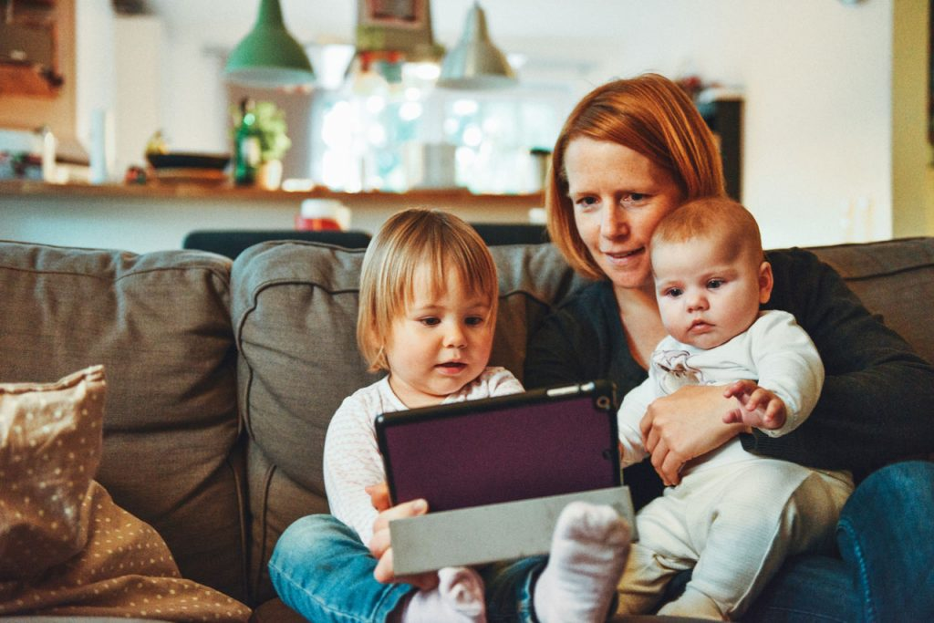 Two young children and their mother are using a tablet.