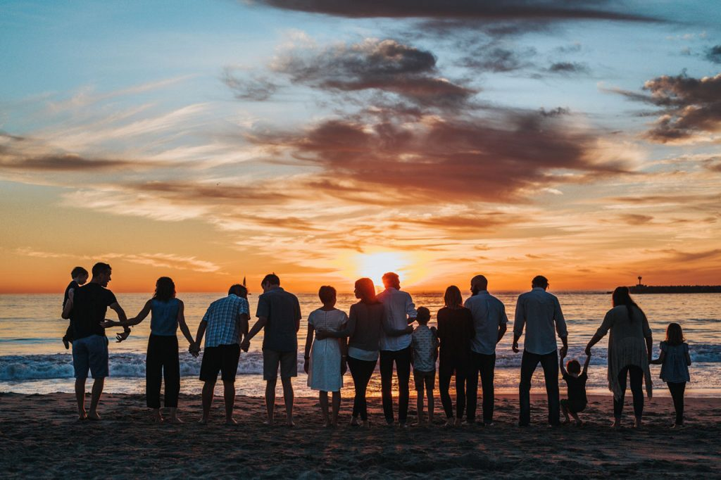 A group of families experiencing a beautiful sunset at the beach.